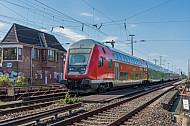 Ein moderner Doppelstockzug der Deutschen Bahn passiert ein altes Stellwerk in Hamburg-Eidelstedt