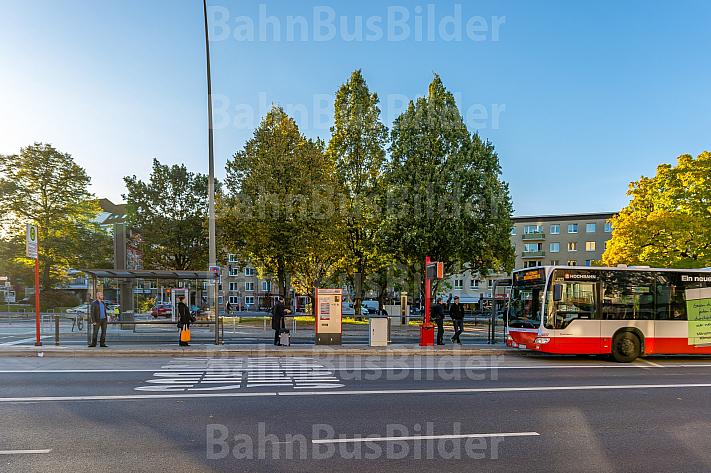 Menschen warten an einer Haltestelle auf einen Bus