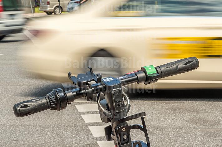 Ein E-Scooter steht an einer Ampel. Im Hintergrund kreuzt ein Taxi.