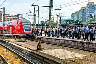 Menschen warten im Hamburger Hauptbahnhof auf einen Regionalexpress nach Lübeck