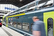 Ein Mensch läuft im Hamburger Hauptbahnhof vor einem Doppelstockzug der Deutschen Bahn