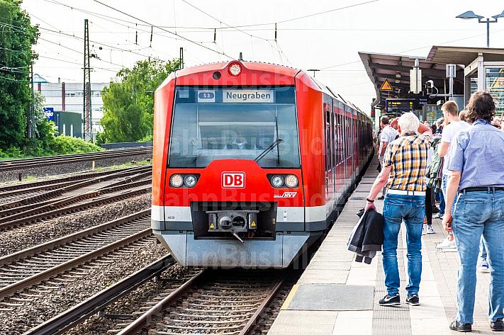 Menschen warten am S-Bahnhof Eidelstedt in Hamburg auf einen einfahrenden Zug der Linie S3