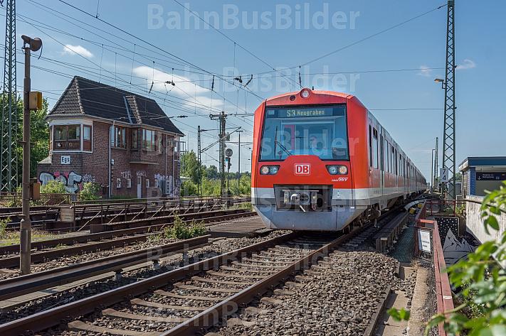 Ein S-Bahn-Zug der Baureihe 474 fährt in den Bahnhof Elbgaustraße ein. Im Hintergrund ein altes Stellwerk