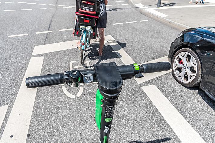 Ein E-Scooter steht auf einer Radfahrspur in Hamburg an einer Ampel hinter einem Radfahrer